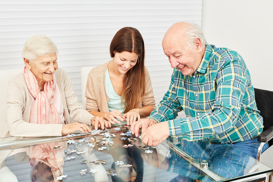 Two seniors and a young lady having fun playing puzzle at home