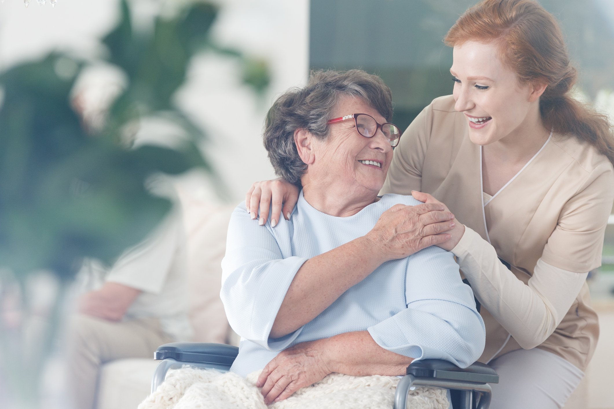 senior in assisted living home happily chats with caregiver